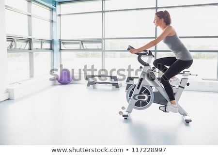 smiling woman riding an exercise bike in gym stock photo © boggy