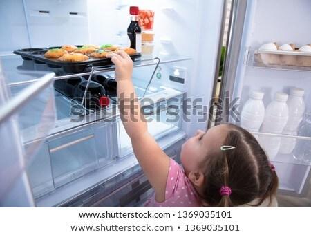 Menina alcançar fora geladeira bonitinho Foto stock © AndreyPopov