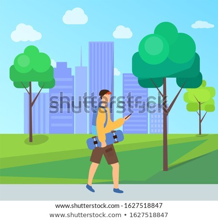 man holding skateboard walking in city park trees stock photo © robuart