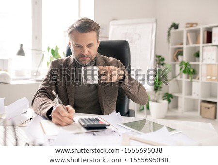 Mature accountant with pen and cup of coffee making calculations by workplace Stock photo © pressmaster
