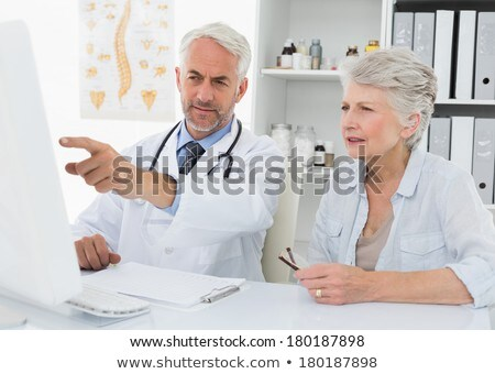 front view of matured Caucasian male doctor showing medical report to the senior mixed race female p Stock photo © wavebreak_media