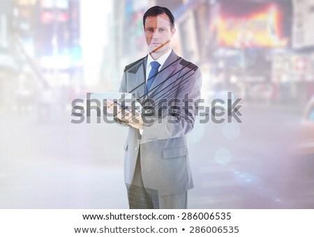 Serious charismatic businessman holding a tablet computer Stock photo © wavebreak_media