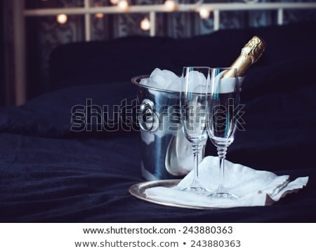 Bottle and two glasses full of sparkling champagne wine with golden decoration Stock photo © dash