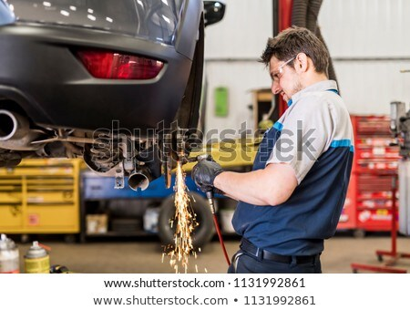 Handsome mechanic job in uniform working on car making spark Stock photo © Lopolo
