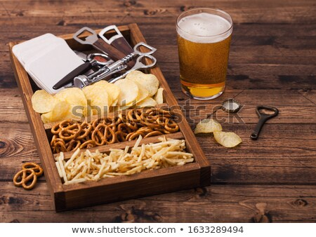 Glass of lager beer with potato crisps snack on vintage wooden board on black background. Beer and s stock photo © DenisMArt