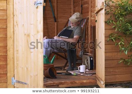 Człowiek posiedzenia leżak objętych papieru Zdjęcia stock © gemphoto