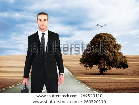 Stock photo: Composite image of businessman holding briefcase