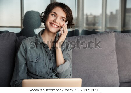 Image of woman typing on notebook and cellphone while sitting on mat Stock photo © deandrobot