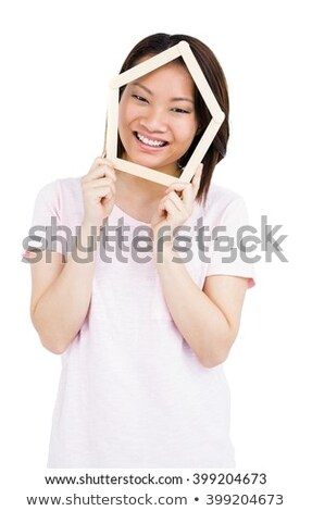 Young woman holding house shaped popsicle sticks on face Stock photo © wavebreak_media