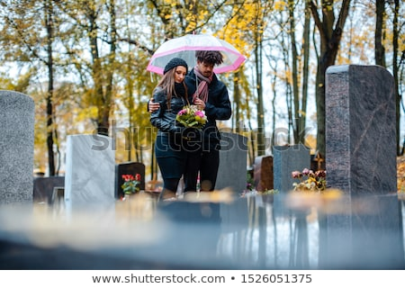 Couple mourning a deceased loved one on cemetery in fall Stock photo © Kzenon