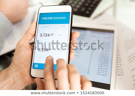 hands of businessperson with smartphone scrolling through online banking account stock photo © pressmaster