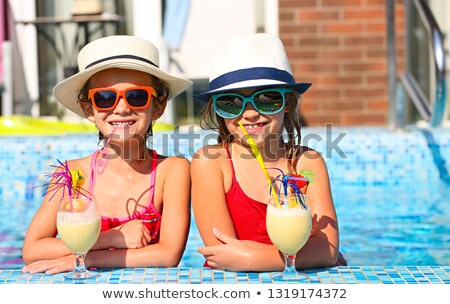 Two happy little girls in sunglasses with cocktails wearing hats Stock photo © dashapetrenko
