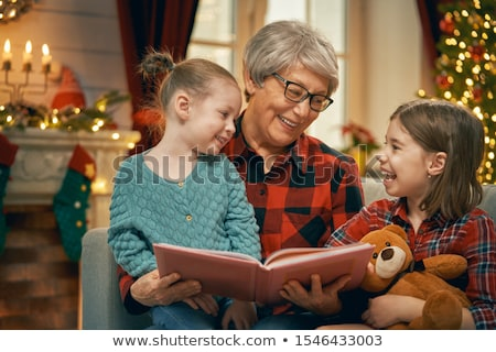 Grandmother reading  to granddaughters near Christmas tree. Stock photo © choreograph