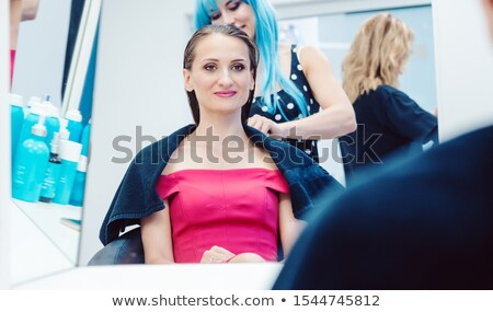 Customer getting a hairdo competently carried out by stylist Stock photo © Kzenon