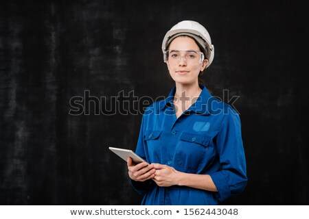 Pretty young specialist in hardhat and blue workwear using touchpad in isolation Stock photo © pressmaster