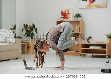 Pretty girl with dreadlocks standing on hands in front of laptop Stock photo © pressmaster
