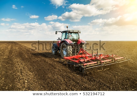 Tractor cultivating field in spring Stock photo © simazoran