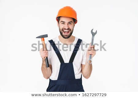 Emotional young man builder in helmet holding hammer. Stock photo © deandrobot