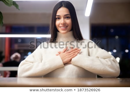 Portrait of lovely multinational women holding hands on chests Stock photo © deandrobot