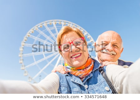 Two elderly couple looking at photos on digital camera Stock photo © photography33