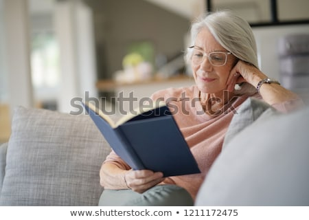 Stock photo: Happy senior woman with glasses reading book at home