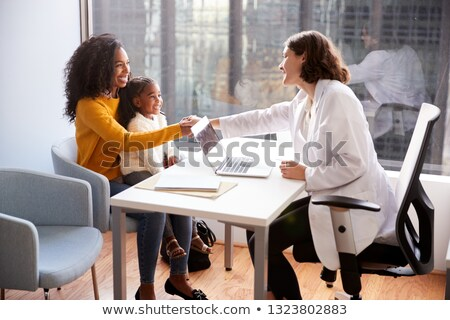 Pediatrician shaking hand with girl child patient Stock photo © mangostock