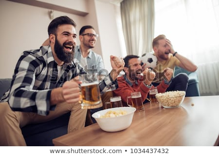 friends drinking beer at home and watching tv stock photo © wavebreak_media
