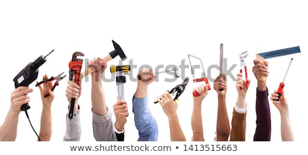 Woman holding a saw and a hammer against white background Stock photo © wavebreak_media