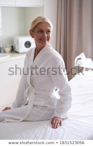 Woman on spa or massage sitting on table and waiting for masseur Stock photo © HASLOO