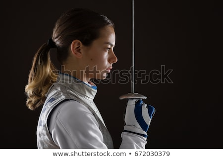 Stock photo: Young woman fencer with epee