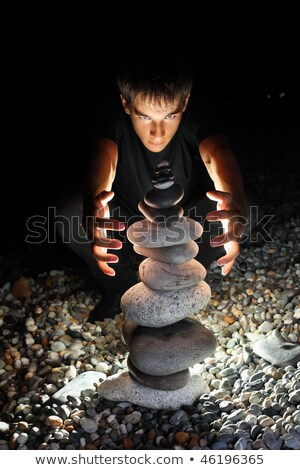 teenager boy conjuring near pyramid from pebble on stony seacoas Stock photo © Paha_L