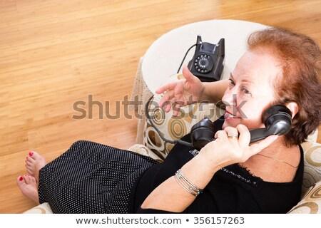 Grandma chatting on an old rotary telephone Stock photo © ozgur