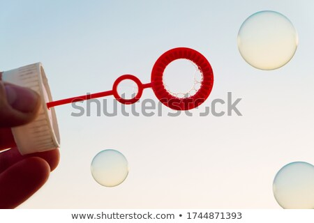 Fingers hold blue soap bubbles Stock photo © ldambies