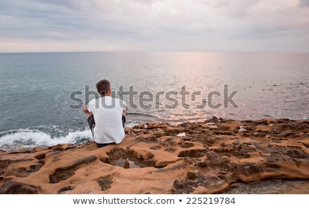 Young handsome man athlete standing at the rocky beach Stock photo © deandrobot