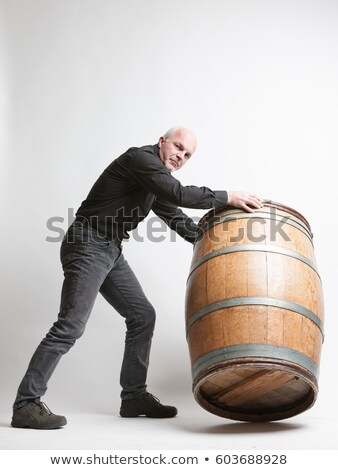 Man moving a large oak wine or beer barrel Stock photo © Giulio_Fornasar