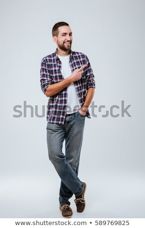 vertical image of smiling hipster pointing away stock photo © deandrobot
