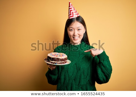 Young girl wearing party hat looking at cake smiling Stock photo © monkey_business