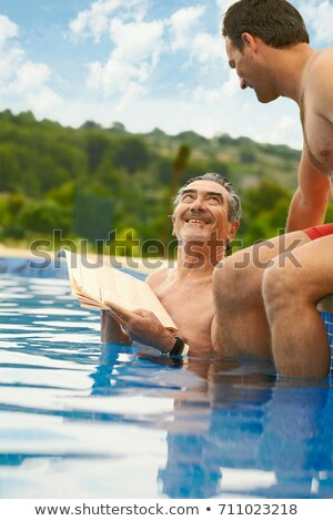 Older man reading news in swimming pool Stock photo © IS2