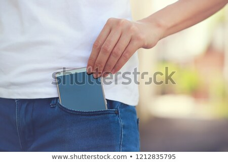 Young woman holding her buttocks in denim jeans Stock photo © Giulio_Fornasar