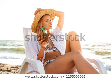 photo of stunning blonde woman 20s in straw hat drinking exotic stock photo © deandrobot