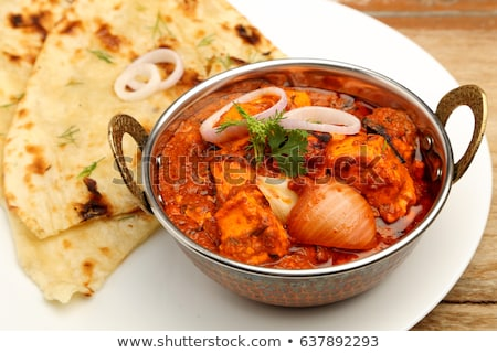 Indian Food or Indian curry in a copper brass serving bowl with nan bread or roti Stock photo © galitskaya