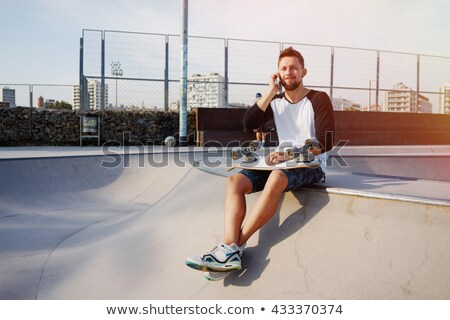 Young skater guy sit in the park with skateboard using mobile phone. Stock photo © deandrobot