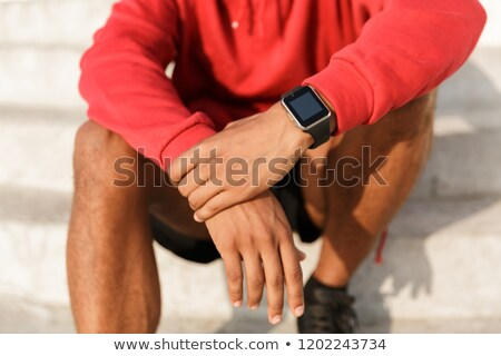 Close up of african man in hoodie sitting outdoors Stock photo © deandrobot