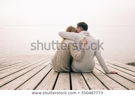 loving couple sitting on the pier on lake stock photo © boggy