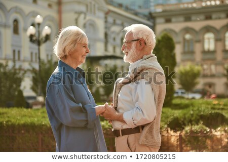 Married couple smiling, and looking at each other while standing Stock photo © deandrobot