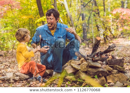 Happy father doing barbecue with his son on an autumn day Stock photo © galitskaya