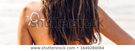 sun drawn with sunscreen lotion on womans back stock photo © andreypopov