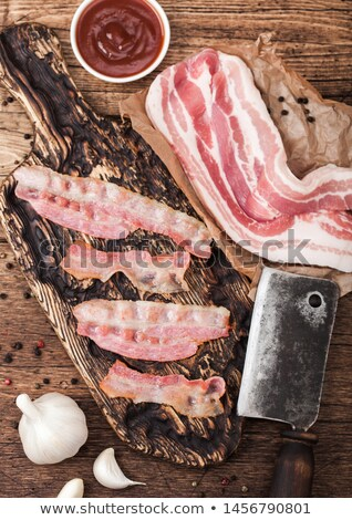 Grilled bacon strips on vintage wooden board with raw fresh smoked pork bacon on butchers paper with Stock photo © DenisMArt
