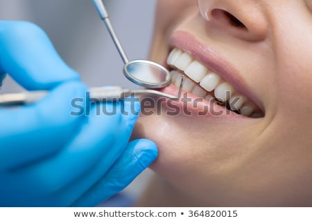 Woman's smile. Healthy white woman's teeth and a dentist mouth mirror closeup. Dental hygiene, oral  Stock photo © serdechny