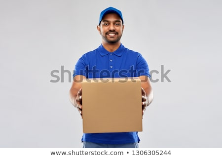 happy indian delivery man with parcel box in blue Stock photo © dolgachov